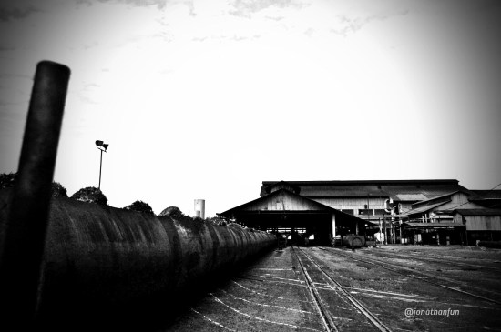 The view from the Marshaling Yard towards the Main Process Building. Fresh Fruit Bunches are fed into steel cages like those on the left, and marshaled into the Sterilizer Machines for cooking.