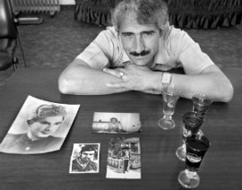 Ali Sheqer Pashkaj poses with family photos and glasses from World War II. Photo by Norman Gershman.