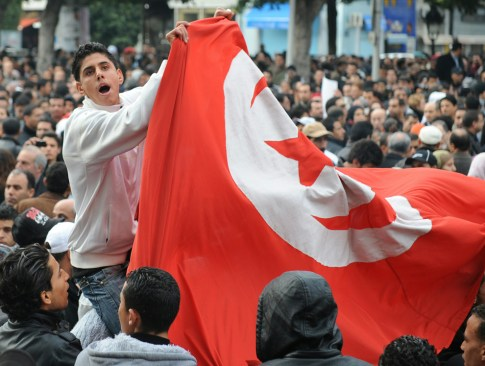 Tunisian pro-government demonstrators hold a national flag during a protest on Habib Bourguiba Avenue in Tunis January 25, 2011. (FETHI BELAID/AFP/Getty Images)