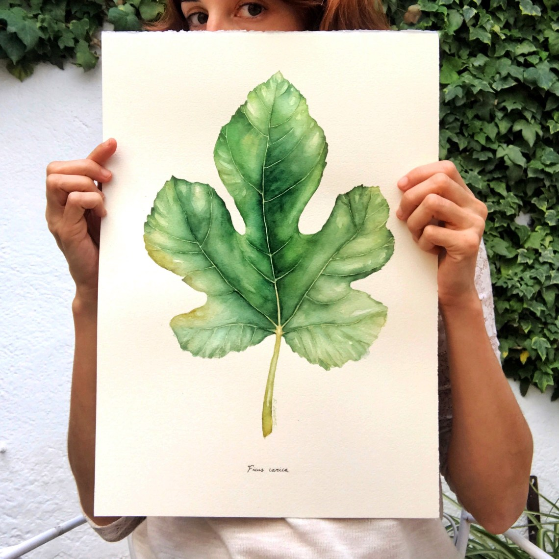 photo of lozano holding a piece of her watercolour art