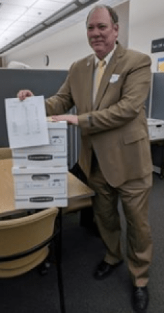 Bill Gelineau in tan suit standing in office, posing with his box of petitions, 2018 candidate for governor of Michigan (color photo)