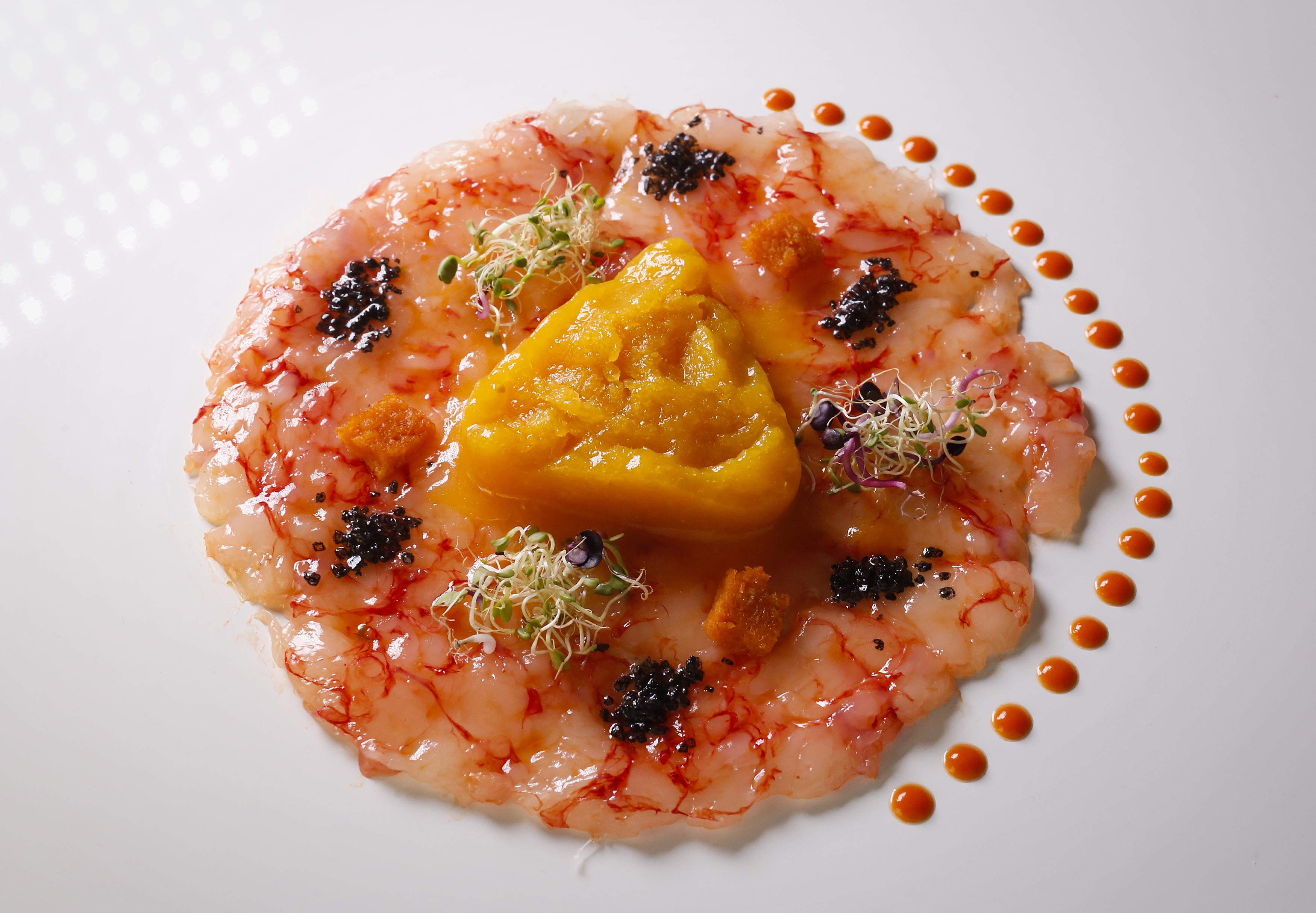 Carpaccio di gamberi rossi, sfumature di pomodoro rosso e giallo, germogli e sale nero di Cipro