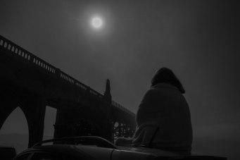 A black and white shot of the eclipse being watched by an onlooker. Photo: Keith James