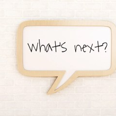 """Image of a chat bubble in a neutral background saying, """"What's Next""""."""