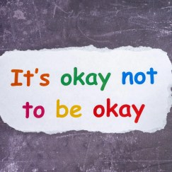 """Image of mutli-colored (orange, yellow, red, green, and blue) text reading """"It's OK not to be okay"""" amongst a white background that looks like it's been scrapped away on top of a grey background."""