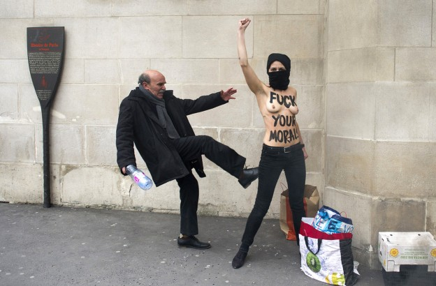 A man kicks a topless Femen activist, as she raises her fist to protest against Islamists in front of the Great Mosque of Paris, on April 3, 2013. (Fred Dufour/AFP/Getty Images)