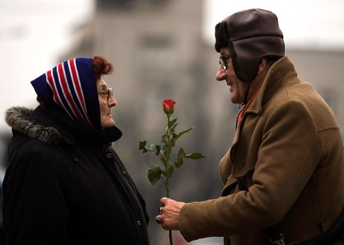a man offers a rose to a woman