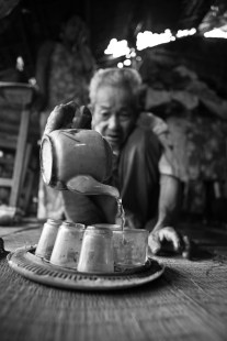 The young girl in the background is supported by the ADAPT Program to prevent human trafficking. She is the only one taking care of her grandfather who is pouring tea and opening his crumbling home to us near the border with Cambodia. Vietnam. 2007