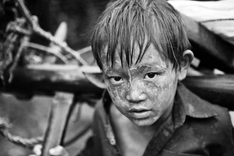 After a long day in the muddy paddy fields this young boy is returning home under the rain. On the road to Sapa. Vietnam. 2007