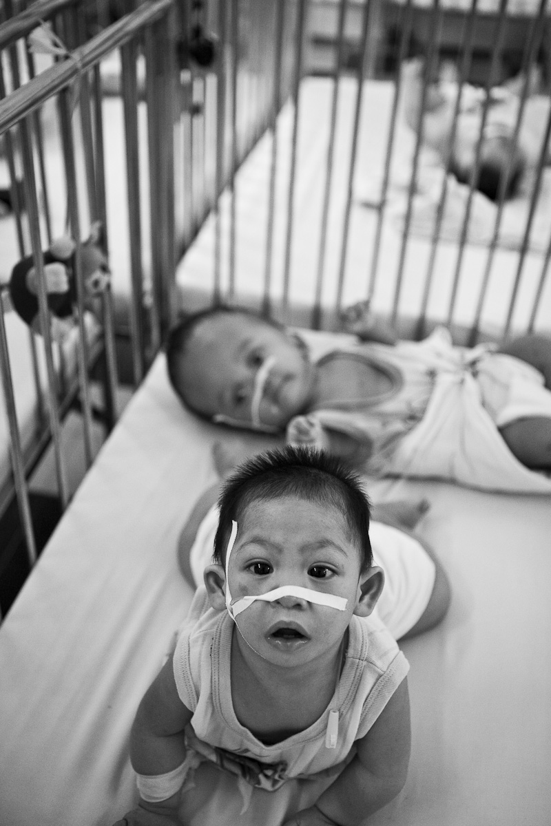 Two young boys, like hundreds of others, spending their days in the metal cribs at the GoVap Orphanage. Ho Chi Minh City. Vietnam. 2007