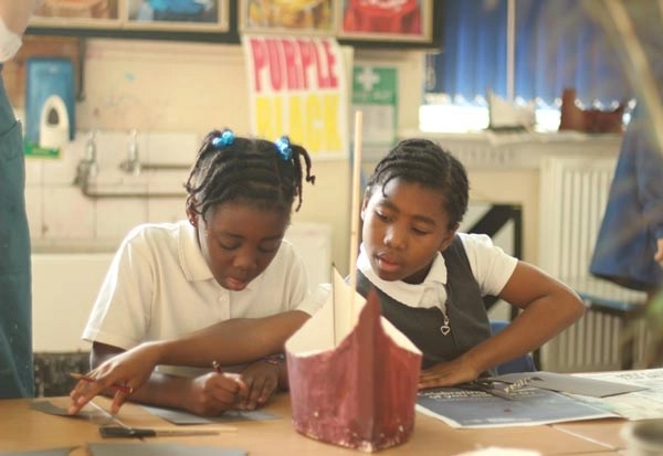 Two girls making a boat within an art class