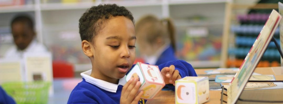 Young boy playing with letter blocks in his English lesson