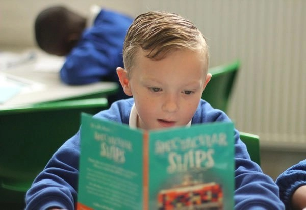 Boy enjoying reading a book in his English lesson