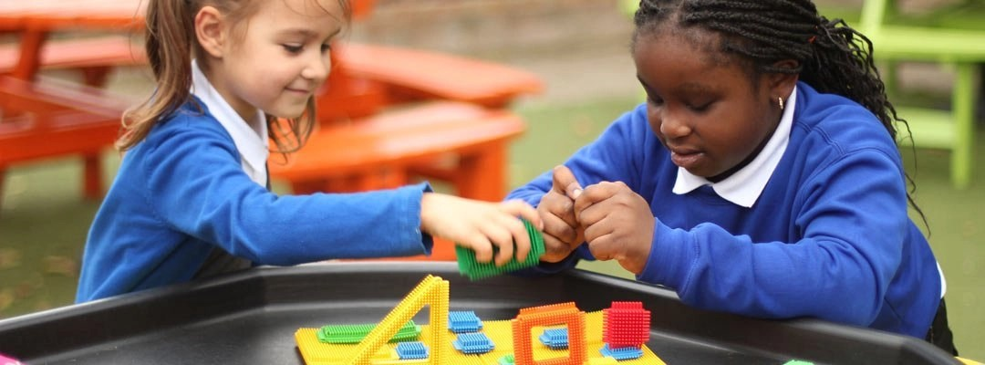 Two girls using coloured blocks in a science lesson