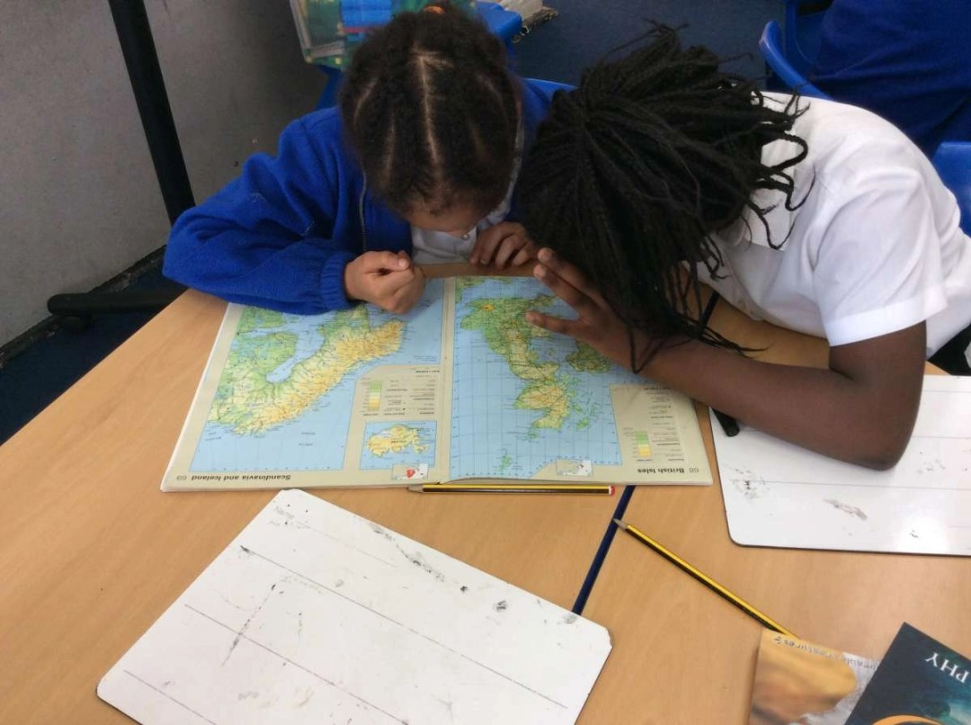 Children listening to a teacher in a Geography lesson