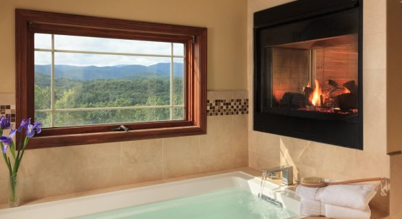 soaking tub filled with water and fluffy towels. Gas see thru fireplace and a window to look out at the view of mountains