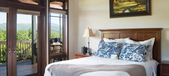 A tall backed wooden bed with blue throws accentuates this bedroom with it's floor to ceiling windows and exterior entry.