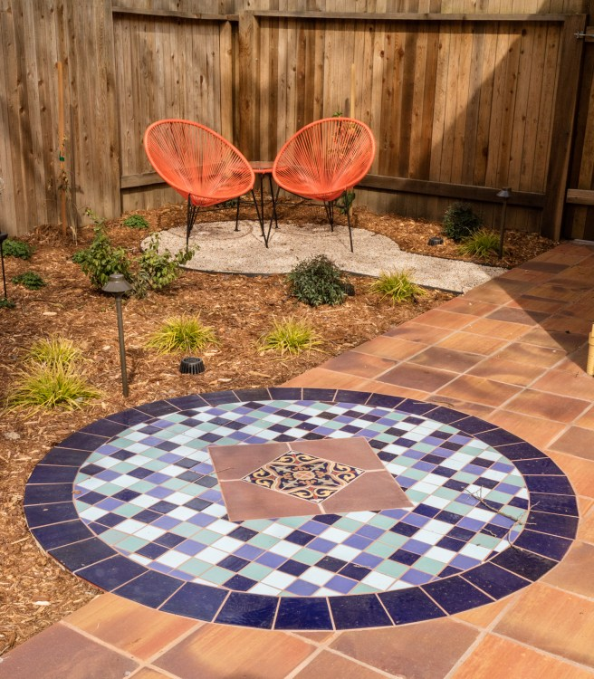 Colorful tiles create a junction accent point. In time, shrubs will grow, separating the seating area from the patio.