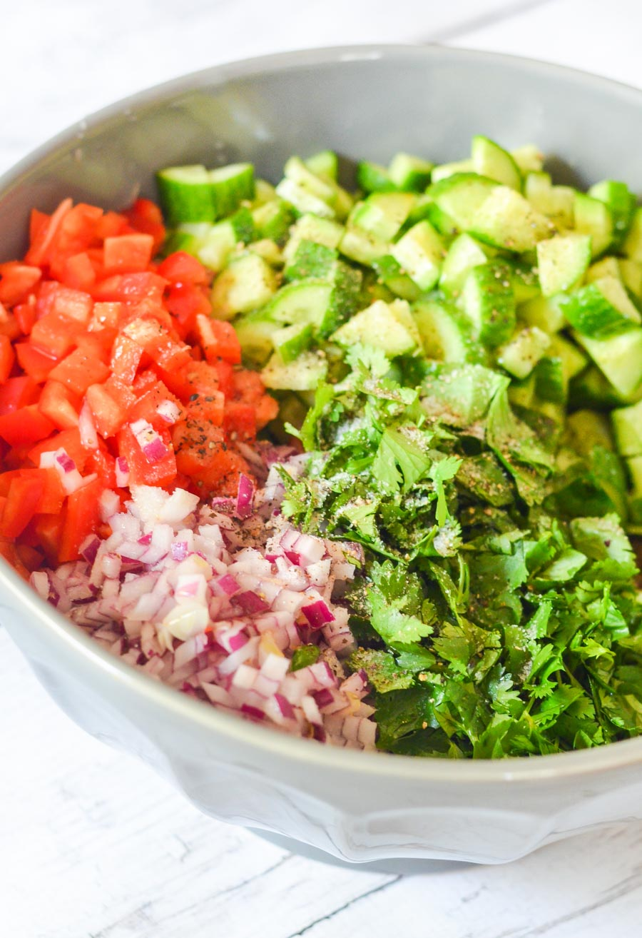 Cucumber, Red Pepper, Cilantro + Onion chopped into a mixing bowl - unmixed