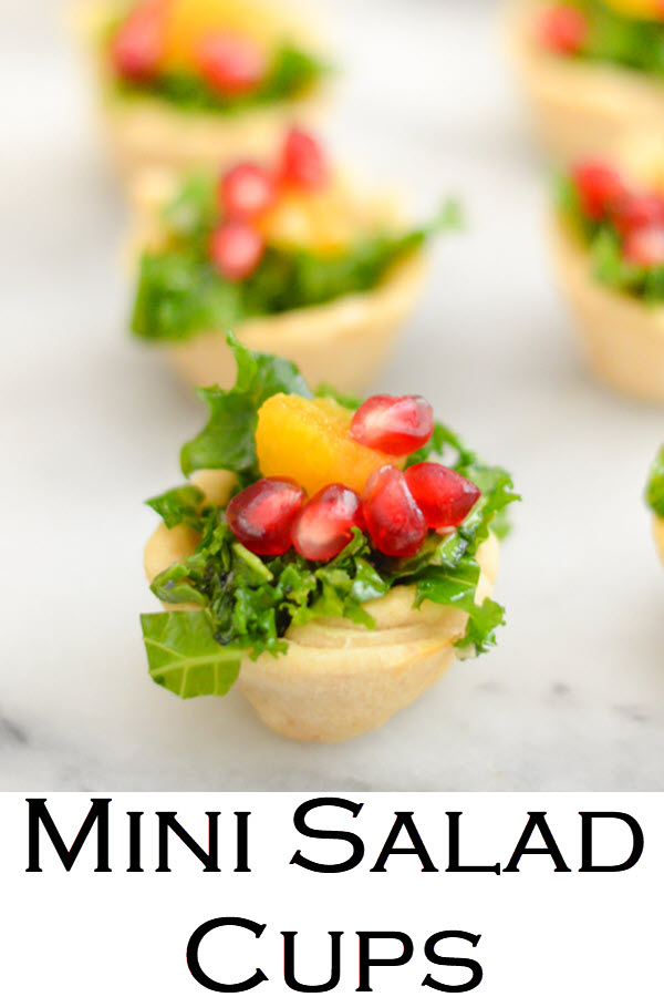 Mini Salad Cups - Bite Size Appetizers. A delicious kale salad recipe with pomegranate seeds and orange segments, this mix is great for any holiday meal. Place salad bits in homemade mini tart crusts for festive bite size appetizers. #LMrecipes #salad #thanksgiving #friendsgiving #kale #pomegranate #bitesize #holidays #christmas #appetizers #partyfood
