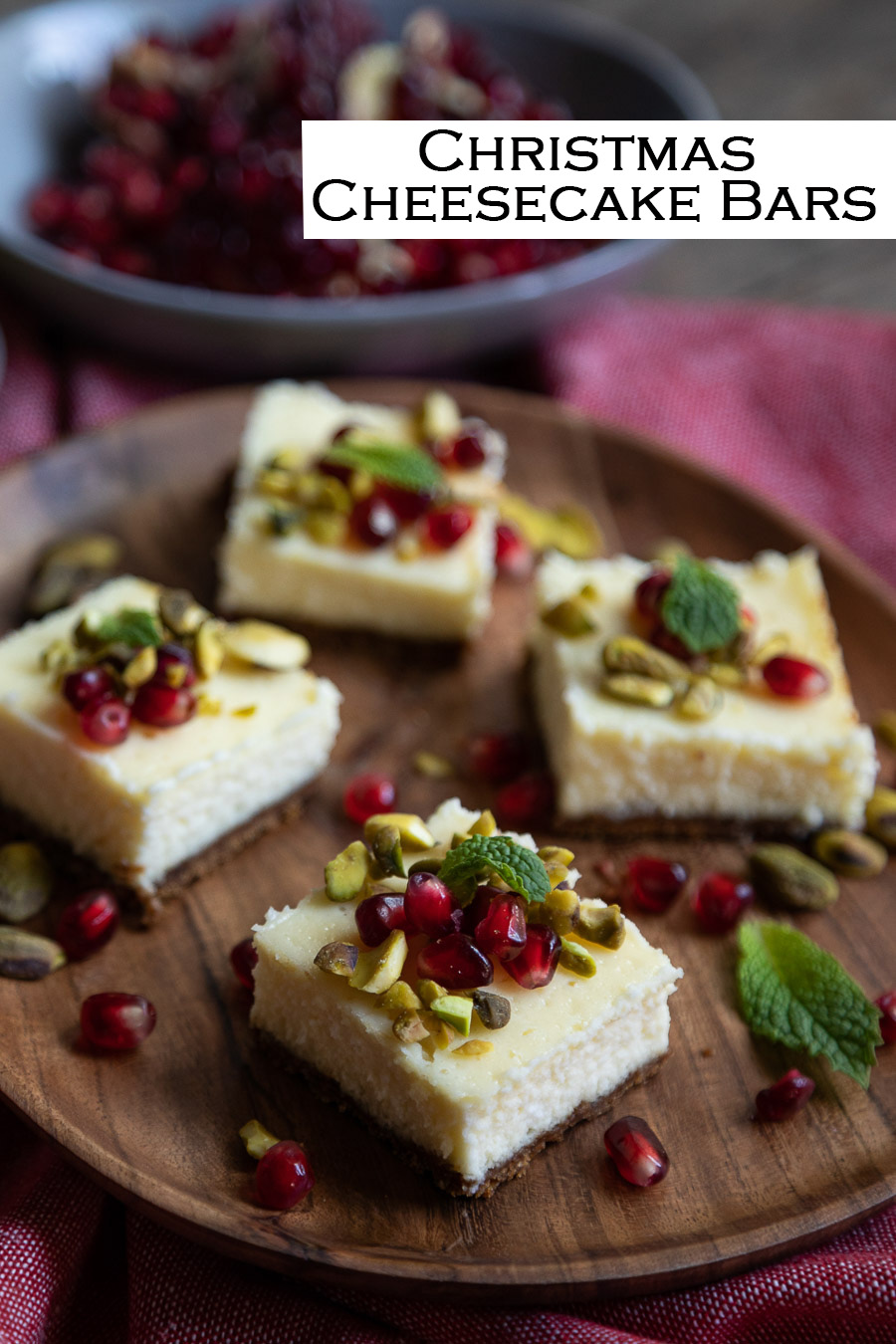 Christmas Cheesecake Bars. Gingersnap cookie crust with creamy cheesecake. Topped with red and green pomegranate arils, chopped pistachios, and mint leaves.