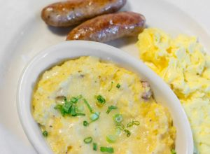 """Twice-baked"" Creamy Grits with housemade bacon, white cheddar and green onions, served with scrambled eggs; one side"