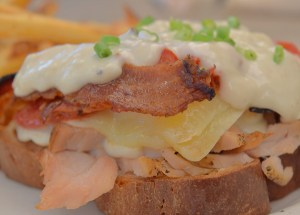 Classic Hot Brown roasted turkey breast with bacon, Gruyère, tomato and white sauce; served open-faced on challah