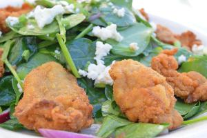 Flash Fried Oyster Salad our classic spinach salad with onions and goat chèvre tossed in warm bacon vinaigrett