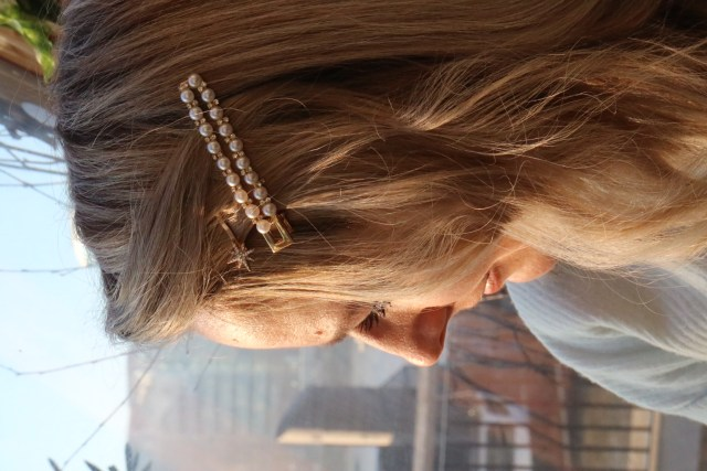 A close up of Lucy's hair with a pearl hair slide and a star hair clip in her hair