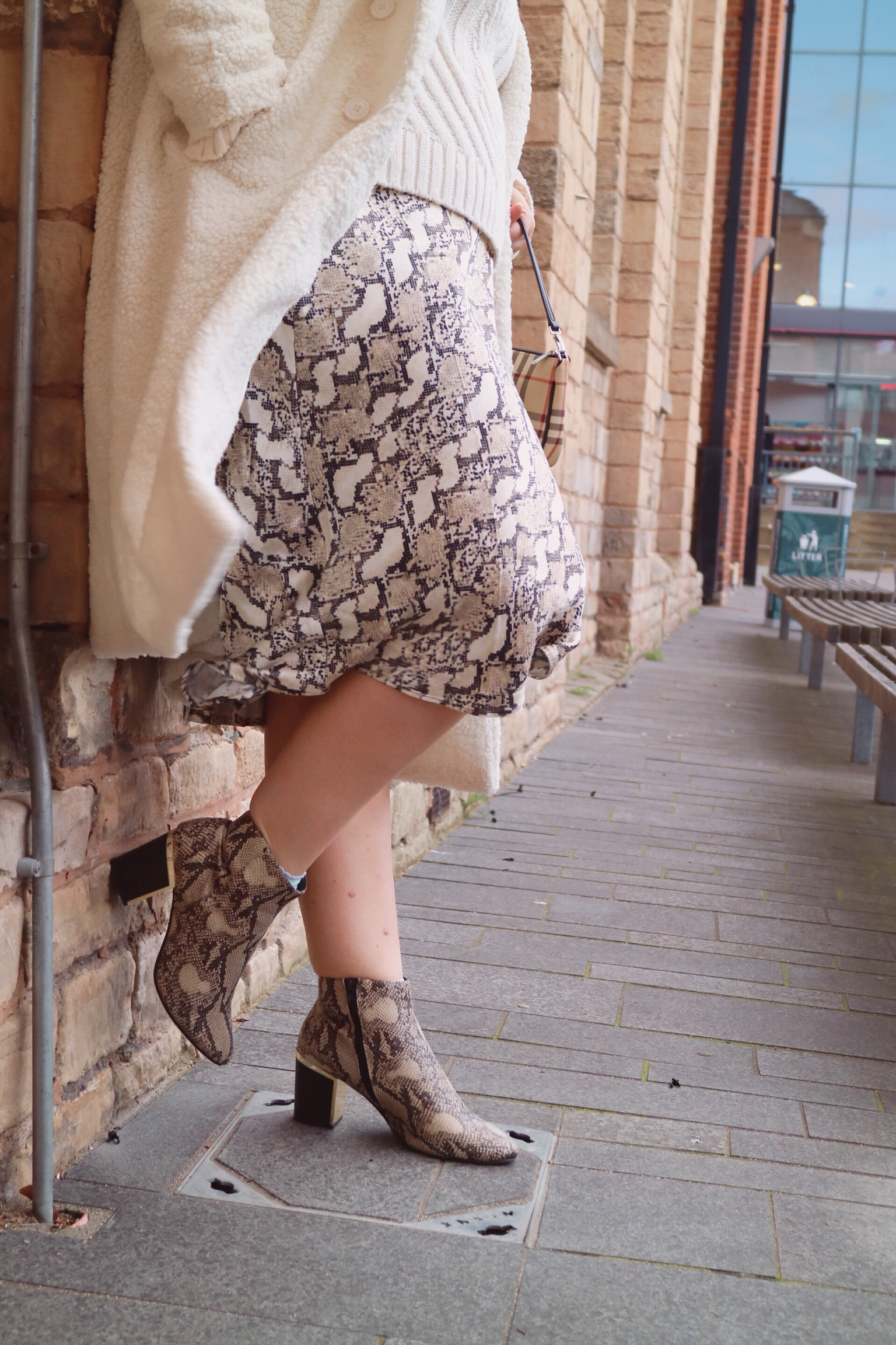 close up of a snake print satin skirt paired with a cream coat and snakeskin ankle boots
