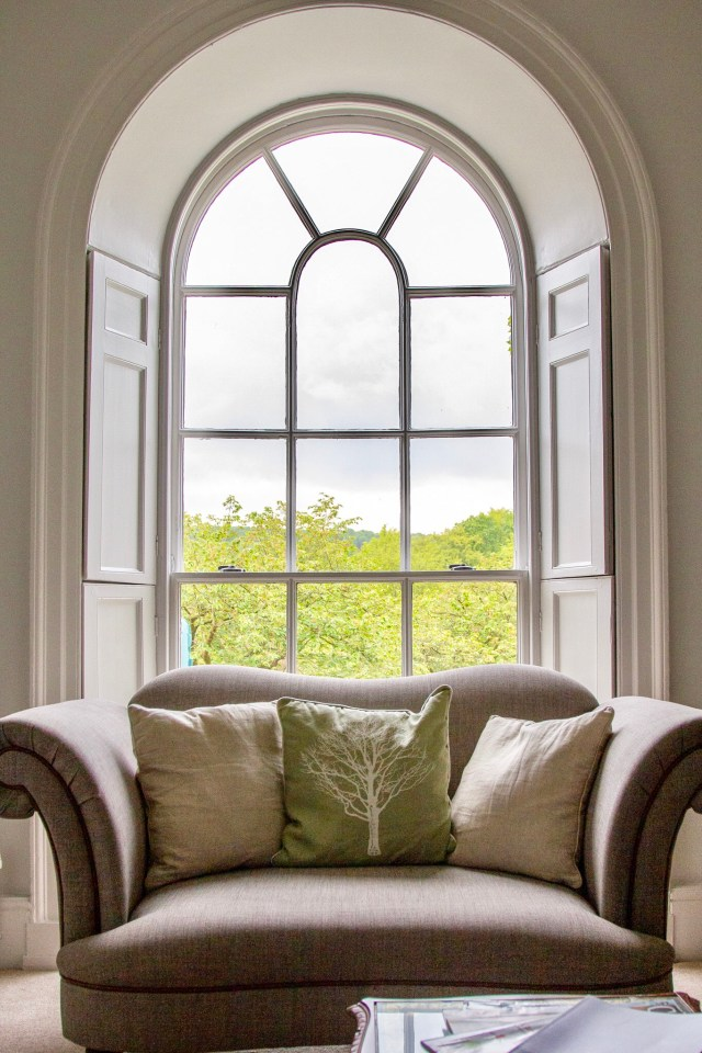arched window with chair in front inside a cottage