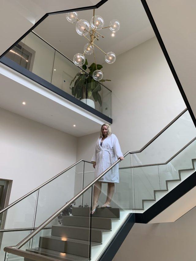 lucy in a dressing gown walking down stairs