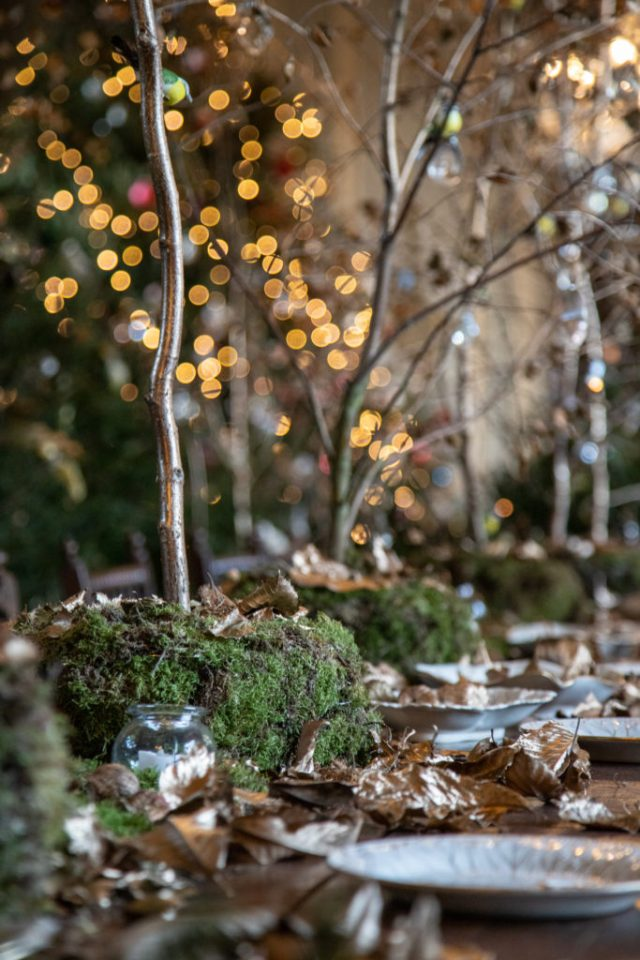dining room table set up with gold leaves and moss with twigged trees coming from it as centrepieces