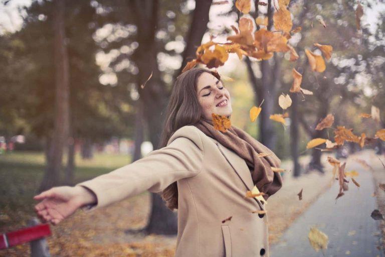 Frau atmet frische Luft im Herbst
