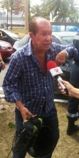 O pai da vítima, o idoso Reinaldo Araújo, segurando o tênis e o capacete do filho