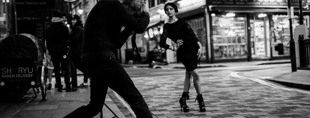 Photographer works with model in Soho, central London, late afternoon. It looks like they are dancing. .