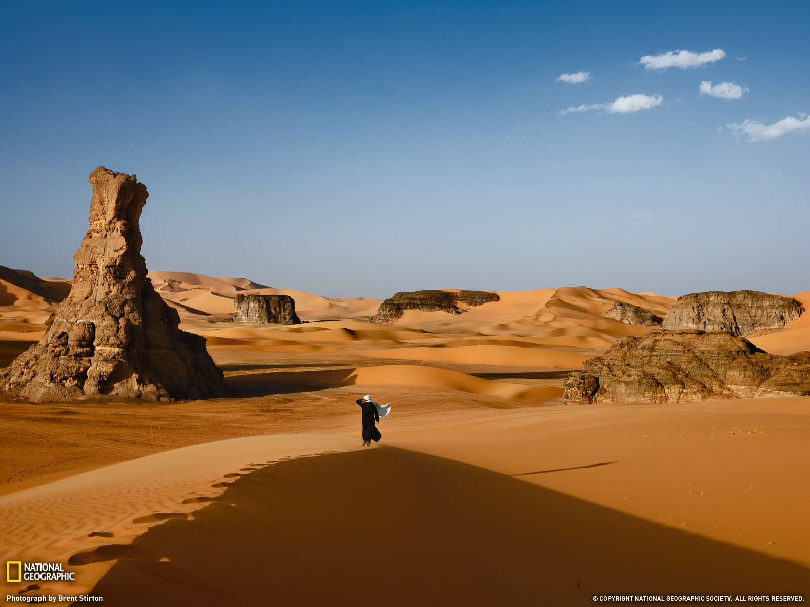 Evening winds stir the robes of a Tuareg striding across Algeria's Tassili-n-Ajjer.