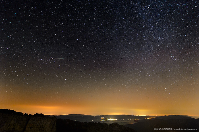 A shooting star races over the night sky above Les Ponts-de-Martel in the Jura mountains in Switzerland on August 15, 2013. Shooting stars, or meteors, are visible paths of small particles racing into the earthÕs atmosphere making the air glow. These meteor showers are called Perseids. The yellow skyglow at the horizon is caused by artificial lighting in the cities Le Locle and La Chaux-de-Fonds.