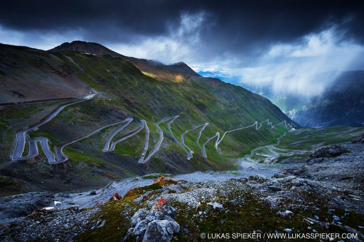 The Stelvio Pass (2757 m) in northern Italy is the highest paved mountain pass in the Eastern Alps, and the second highest in the Alps. It connects the South Tyrol with the Veltlin in Lombardia in Italy and is only 200 meters from the Swiss border. The original road was built in 1820–25 by the Austrian Empire. The seventy-five hairpin turns cover an elevation gain of  1871 meters.
