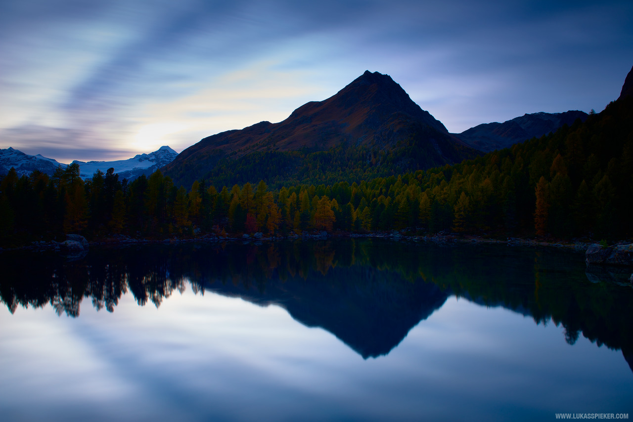 The sun sets over a lake in a small valley in Val Poschiavo in Switzerland's canton Graubünden (Grisons).