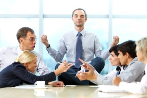 man-meditating-on-office-table-as-colleagues-argue