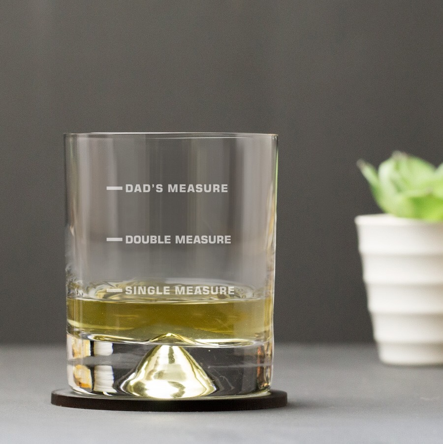 A wide glass, with the words Dads Measure, Double Measure, and Single Measure, printed on the front of it, on a black background.
