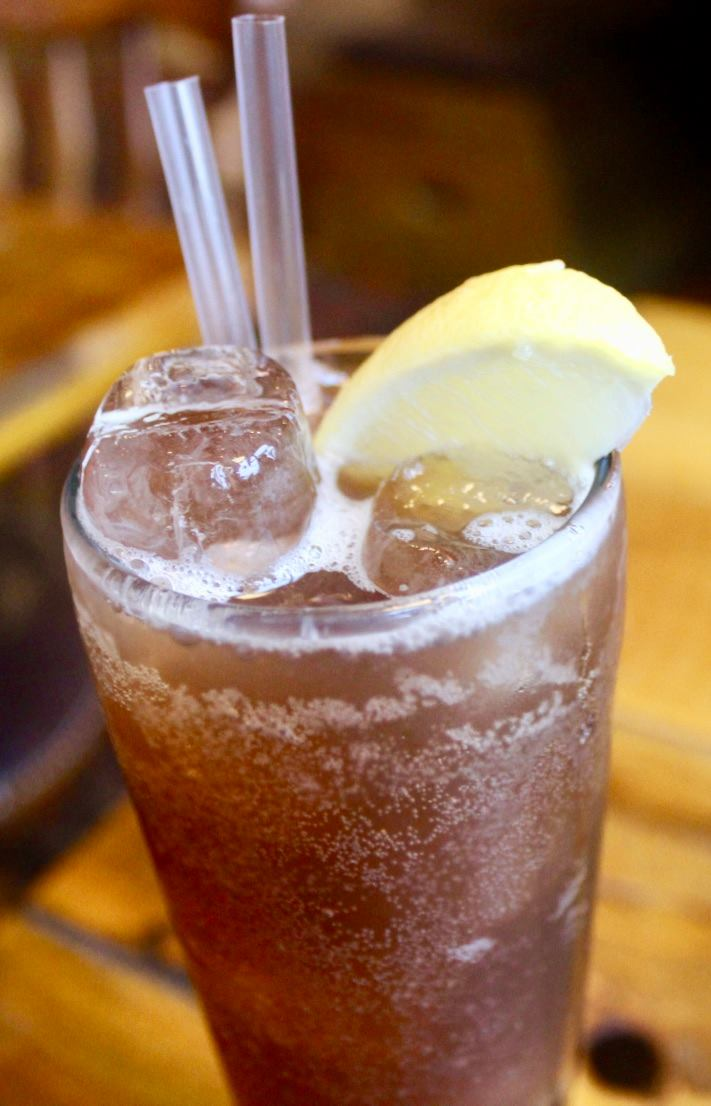 A tall glass full of coloured Cola, with some clear ice cubes at the top of it, with some clear straws and a yellow slice of lemon on the rim of the glass, on a tan background.
