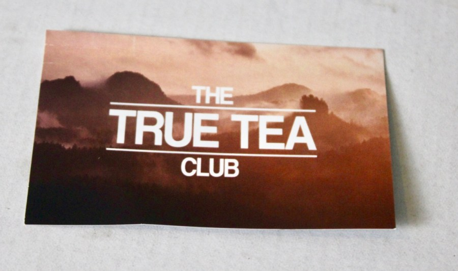 An orange, brown, and pink piece of card that has true tea club written in bold uppercase white writing on it, on a white background.