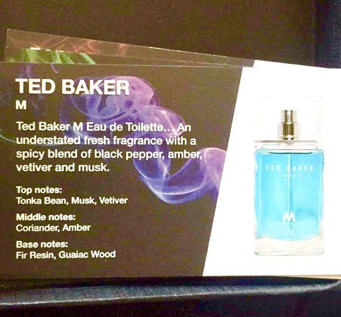 A small Gold rectangular piece of card with a description of the Ted Baker M fragrance written in white writing next to a tall clear glass bottle full of light blue liquid, on a black background