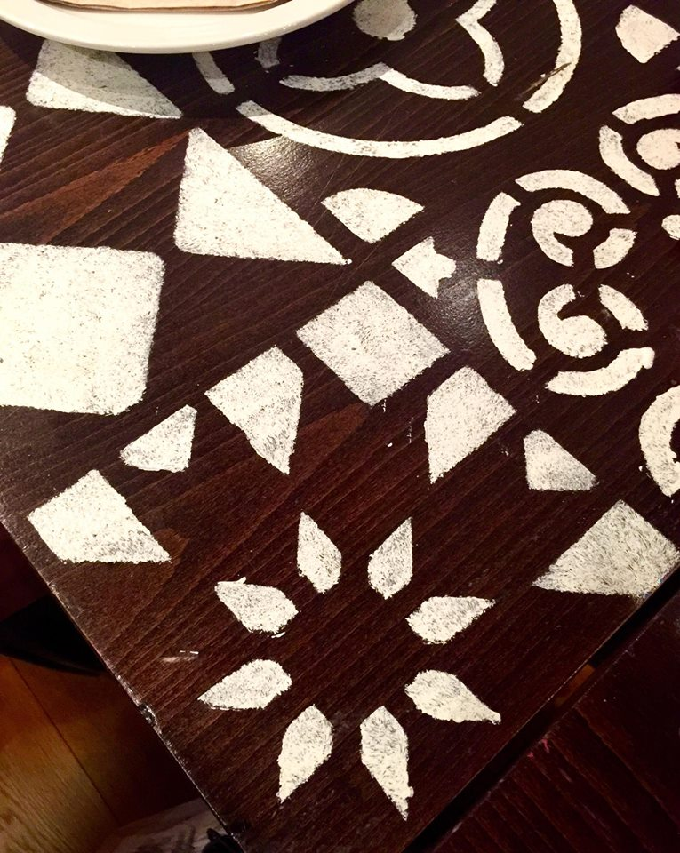 A black table with a white coloured pattern all over it.