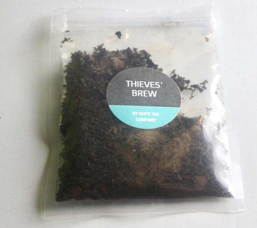 A square clear plastic bag containing some dark black tea leaves with a dark green circular sticker that has Thieves' Brew written in medium white writing and Bev's Tea Company written in smaller white writing on it, on a white background.