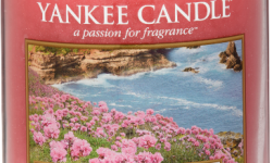 A tall glass jar full of bright Pink coloured wax, with a label that has a picture of some Flowers next to the Sea, and Yankee Candle and Garden by the Sea written in black writing on it, on a white background.