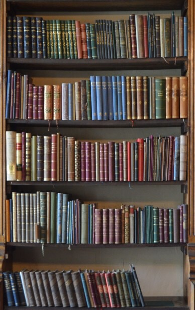 A large wide dark brown wooden bookcase filled with some thin books with various coloured covers, on a dark background.