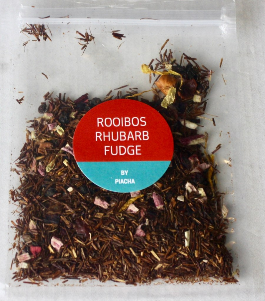 A square clear plastic bag containing some dark brown tea leaves with a dark pink circular sticker that has Rooibos Rhubarb Fudge written in medium white writing and Piacha written in smaller white writing on it, on a white background.